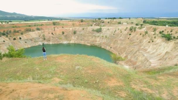 Fit dívka v džínách sedí na okraji opuštěného dolu jámy