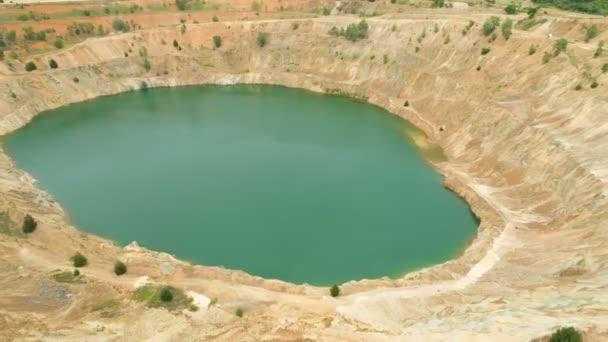 Nerozpoznatelná žena sedící na okraji opuštěné důlní jámy plné vody a fotící