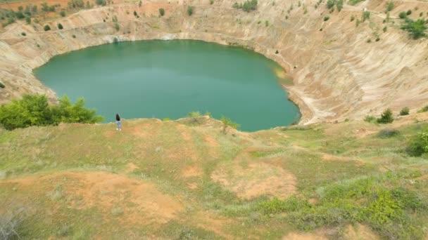 Letecký pohled na osamělou ženu, která se stále nachází v blízkosti opuštěného měděného dolu a těší se z výhledu