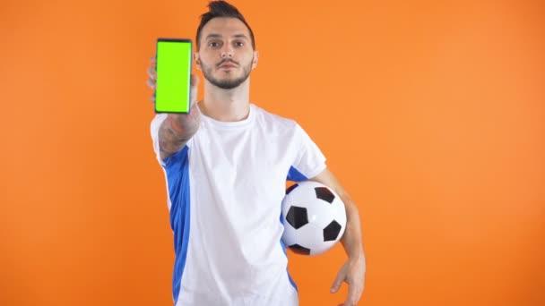 Football Fan In white blue shirt show green screen smartphone orange background