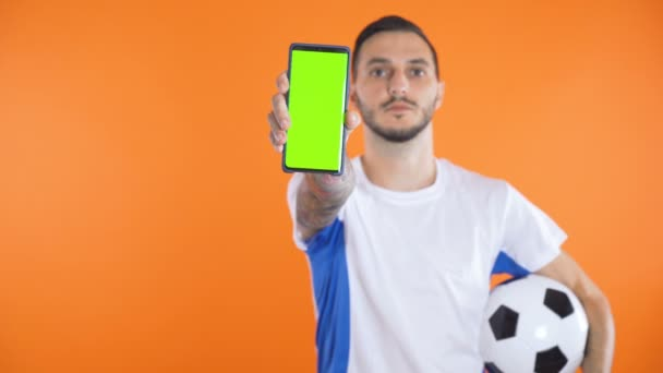 Football Fan In white blue shirt and ball show green screen smartphone orange background