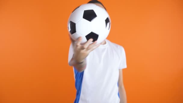 soccer ball in font of white blue shirt soccer fan smiling and succes