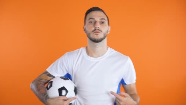 Young soccer player in white blue shirt holding ball and pointing at invisible shirt team logo