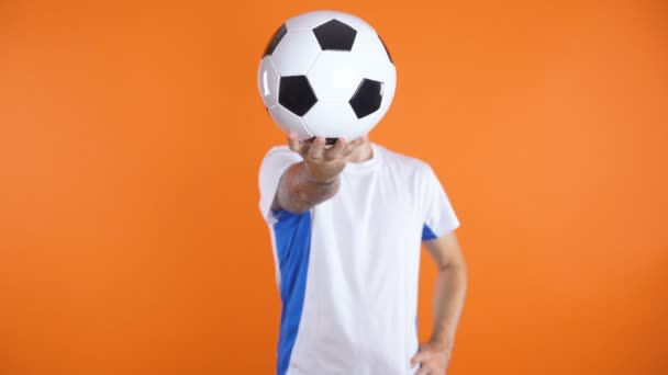 Football Fan In white blue shirt standing still and holding ball in front of his face with one hand