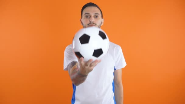 Young soccer player in white blue shirt holding soccer ball in his hands in front of camera with serious face