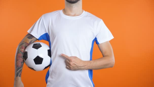 Close shot man hand with pointing finger follows invisible logo on football shirt.