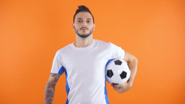 portrait of tatooed Football fan or player holding ball isolated on orange background