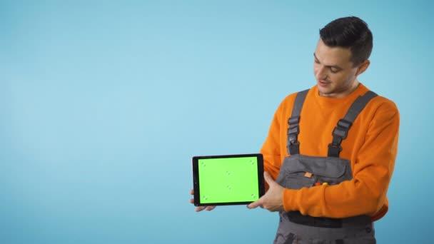 Green Screen Tablet in der Hand mit Kopierraum isoliert auf blauem Hintergrund