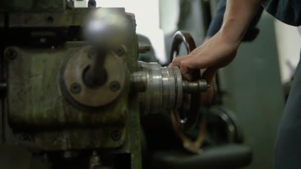 Egy gyári munkás nehéz gépeket üzemeltet egy üzemben. Egy nagy vaskereket forgat. Sok felszerelést látunk a munkahelyén..