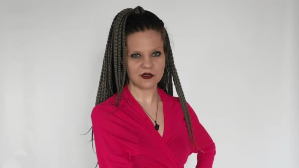 A weird gothic girl in a crimson top with long grey afro braids and dark make up and mascara is lifting an orange dumb-bell. A creative concept for a sport \ fitness center or a sportwear store.