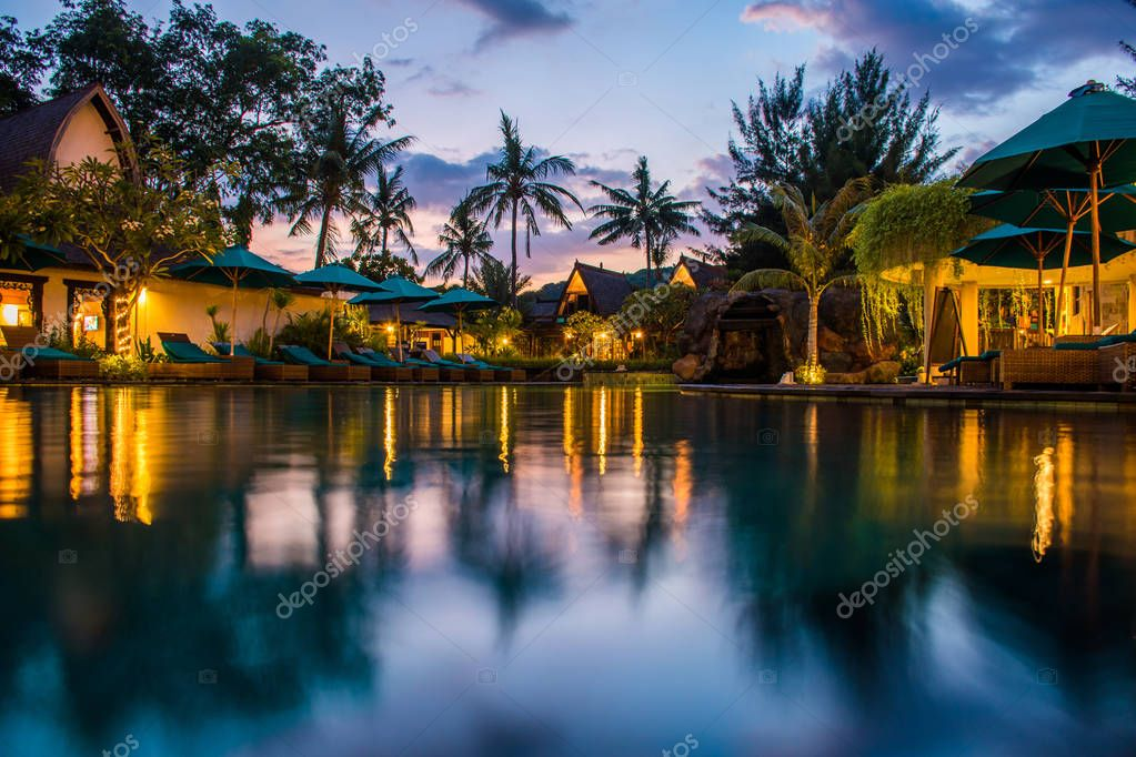 Tropical hotel with swimming pool at night with reflections and palms, Gili Trawangan, Lombok, Indonesia