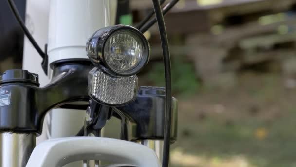moderner Fahrradreifen mit elektrischem Rad-LED-Licht und Motor auf verschwommenem Hintergrund, im Sommer draußen