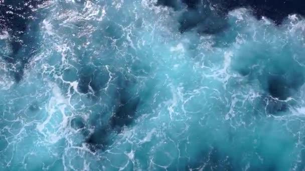 Vlny s pěnou za člunem. Jsou to vlny vln ve vodě. Výhled na hladinu vody z výletní plavby v 4k