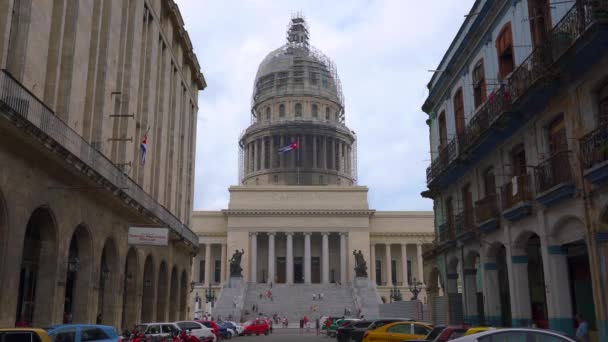 HAVANA, CUBA - MAY 13, 2018 - Street view of the dome of El Capitolio in Old city with people and cars in 4k