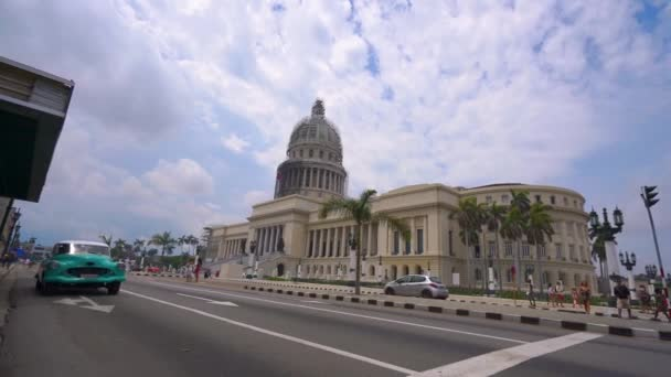 HAVANA, CUBA - MAY 13, 2018 - El Capitolio, or the National Capitol Building with vintage american cars and people on the streets in 4k
