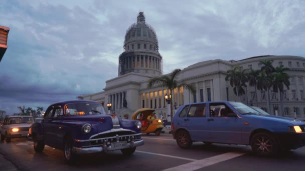 HAVANA, CUBA - MAY 13, 2018 - Vintage american cars on the crossroads near El Capitolio in sunset in 4k