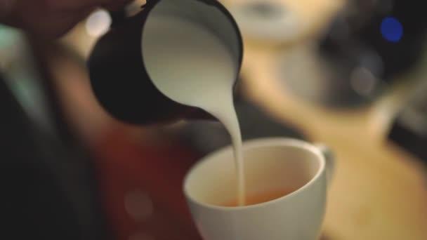 Lassú mozgás a barista öntött tejet a kávé létre egy tökéletes cappuccino vagy latte