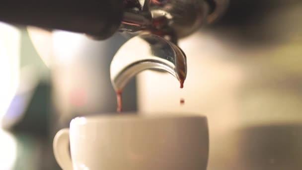Kávéfőző forró eszpresszó kávét tölt egy csésze lassú mozgásban