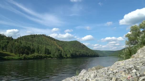 Scenic summer mount landscape with fast moving volumetric clouds above river