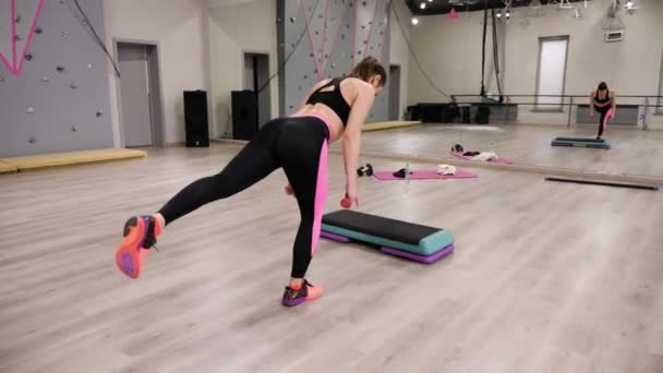 Exciting backside view brunette girl with ponytail exercises with dumbbells  balancing against mirror in gym