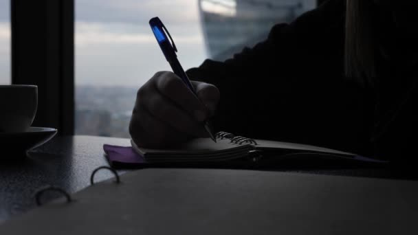 close view lady hand silhouette holds pen and writes in paper diary notebook near white cup against huge window