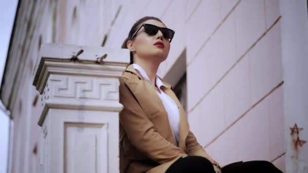 attractive girl in sunglasses sits against building