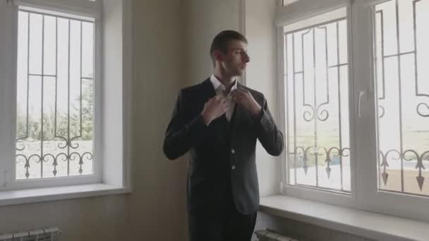 serio giovane in abito corregge colletto camicia bianca