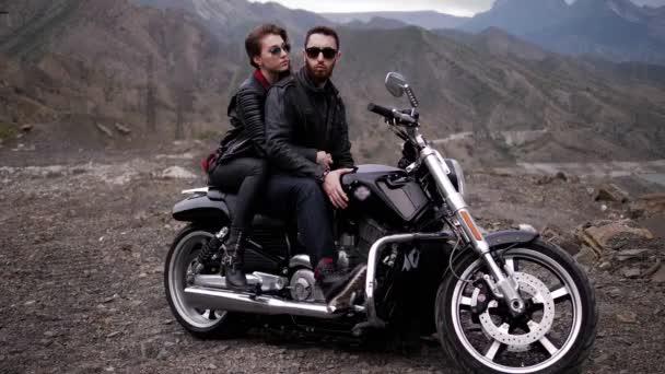 dívka ve stylové černé bundě na motocyklu na motorce s kamenitými svahy