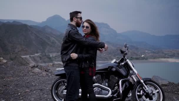 Stylový pár zamilovanej do černé stříbrné motorky a klidné jezero obklopené horami