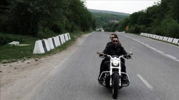 Stylový pár jezdí po horské silnici na černou moderní motocykl s barikamy z bílého kamene