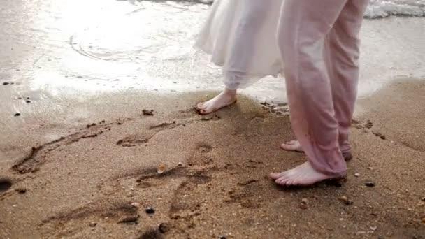 Barfuß-Paar betritt gelben Sandstrand am Meerwasser und hinterlässt Fußspuren