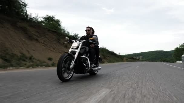 milá dáma s volně tekoucí vlasy, které ve větru zamávala, má vousatý biker jedoucí na moderním motorce