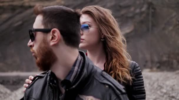 beautiful lady in sunglasses holds hand on bearded man in leather jacket shoulder