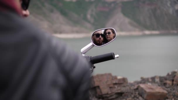 szép pár tükrözi a modern motorkerékpár ezüst tükör ellen, nyugodt hegyi tó este