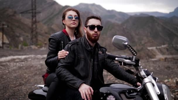 Stylový párek lásky sedí na moderním černém stříbrném motorce proti hnědým skalnatým horám ve večerním