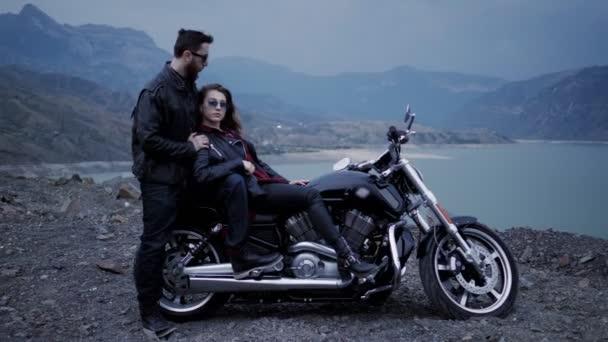 Stylová dáma s dlouhými kudrnatými vlasy sedí na černém motorce a dívá se na vousatého muže v slunečních brýlích na jezero a kopce