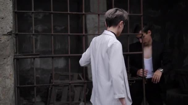 Dame mit Kurzhaarschnitt und Mann im Anzug stehen am Gitter