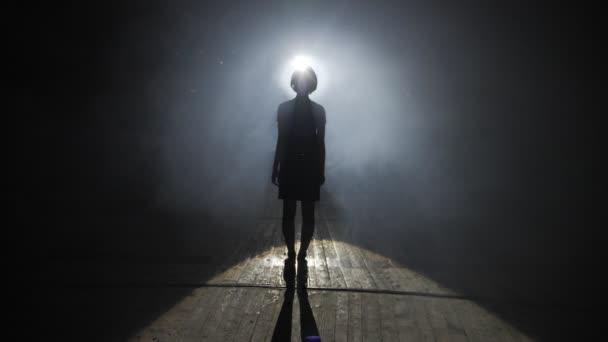 silhouette di donna in piedi sul pavimento contro la luce brillante