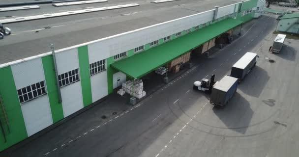 egy teherautó betöltése egy logisztikai központ felülnézetben