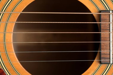 close macro view of the six frets  and sound hole on an acoustic wooden  guitar