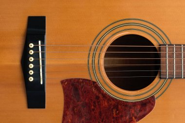 close macro view of the six frets  and sound hole on an acoustic wooden  guitar body