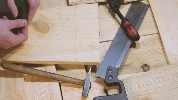 Kalapács, a fűrész és a bilincs feküdjön egy fából készült háttér. Építőipari eszközök