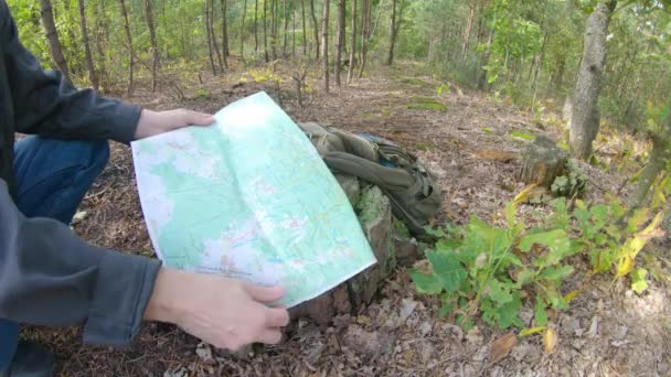 Hiking Man Using Navigation Map and Compass In the Woods. Man explorer searching direction with compass in summer forest. Mans hand holding compass, map in background.