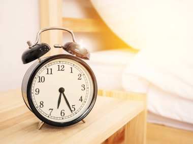 morning time background, retro alarm clock near the bed at home.