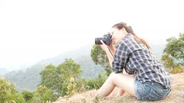 junge aktive asiatische Touristin Reisefotografin mit Rucksack, die mit der Digitalkamera am Aussichtspunkt auf die Bergnatur fotografiert, das Bild auf dem Bildschirm nach dem Foto überprüft und lächelt