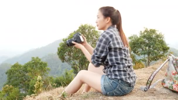 fiatal aktív ázsiai turista nő utazik fotós egy hátizsákot fotózni a digitális fényképezőgép szempontjából a hegyvidéki természet érdekében, ellenőrizze a kép a képernyőn után fotózni, és mosolyog