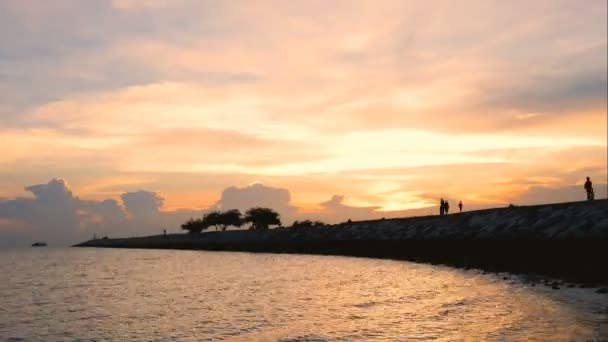 time lapse of silhouette happy people and family walking on the bridge over the sea along edge of sunset beach. spend time together with relax happy life outdoor activity on tropical summer vacations