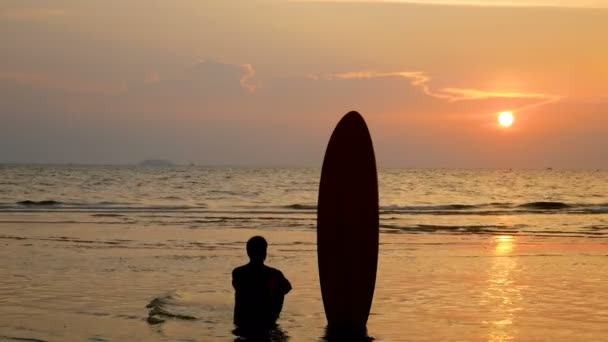 4K. silhouette of surfer man sitting on the sea beach with long surf boards at sunset on tropical beach