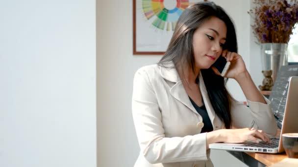 4k Footage, forgalmas üzleti nő dolgozik laptop számítógép és okostelefon a kávézóban kávézóban a város reggel, az üzletemberek életmód. Ázsiai modell a lány 30-as évek