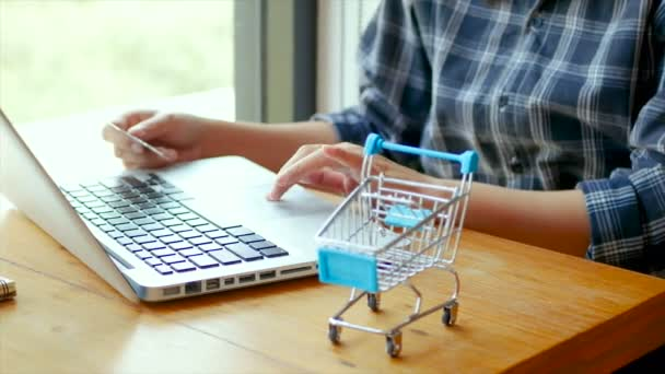 4K footage. online banking , shopping concept. female hand holding a credit card and shopping online. shopping online with credit card at home lifestyle, shopping cart in foreground